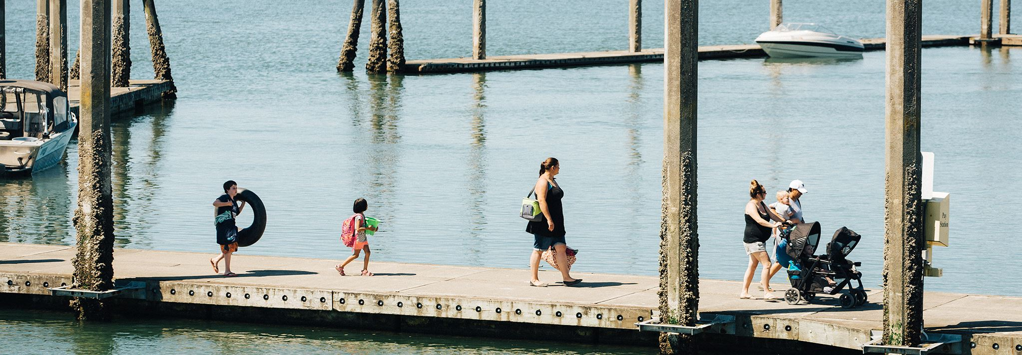 A group of parents and young children walk along the pier carrying their water toys.